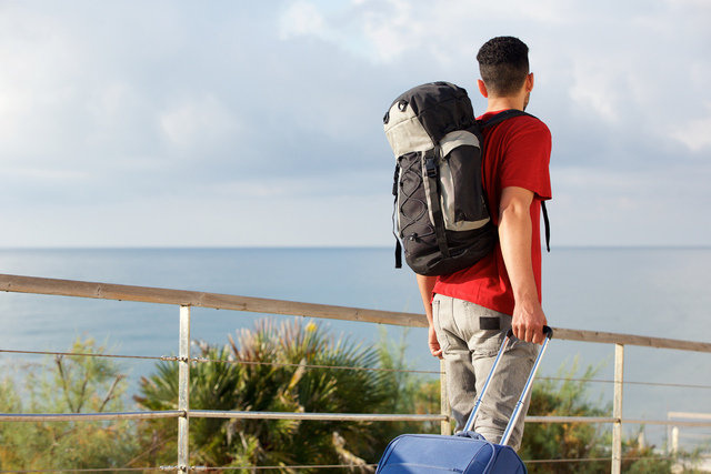 man traveling with backpack and suitcase