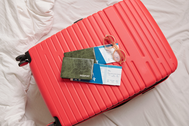 suitcase with sunglasses, passports and airline tickets